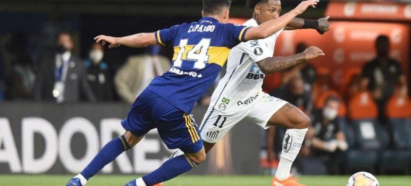 O atacante Marinho tenta passar por um marcador do Boca Juniors no confronto desta quarta na Bombonera